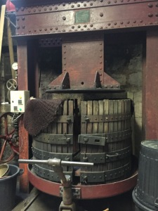 This press is about 100 years old. The chateau purchased a modern press, but ultimately decided to go back to this one because of the quality of juice they can get from it.
